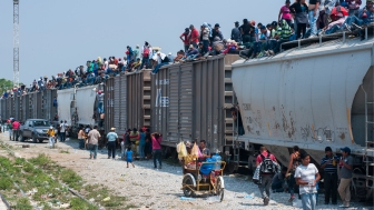 After an irregular entry into Mexico near Ciudad Hidalgo, to move north through the country, to the US border, many Central and South American migrants begin their journey in Arriaga, Chiapas, Mexico, the railhead of the freight train known as 'La Bestia' (The Beast), climbing atop of the rail cars, exposed to the elements and extortion by criminal gangs lying in wait along the route.  Vendors sell food, water and cardboard pallets to lie on for the journey.
